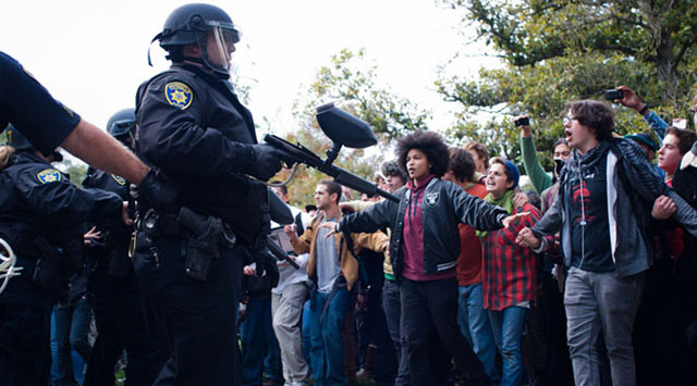 Occupy Davis protesters back away from UC police after the controversial pepper spraying incident on Nov. 18. Police violence against protesters on UC campuses triggered much backlash among the student body, including the alumni that participated in the protest movement. Photo used with permission of Class of 2010 alumnus Gene Ang.