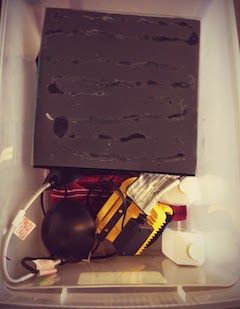 Our homemade cloud chamber consists of a small box with a lid lined with black felt. In order to nudge muons into uncloaking themselves, we douse the felt with isopropanol and heat it from above with my desk lamp.